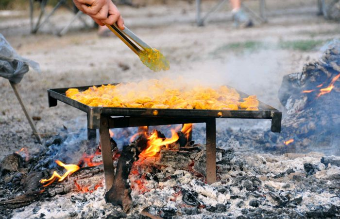 Food being cooked on a hotplate over a campfire.