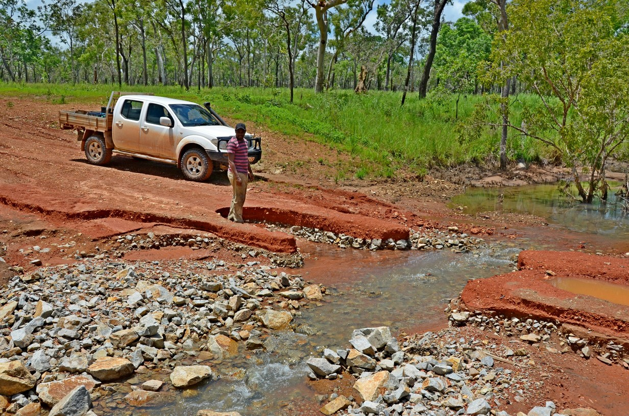 Cape York road with washout and water running across.