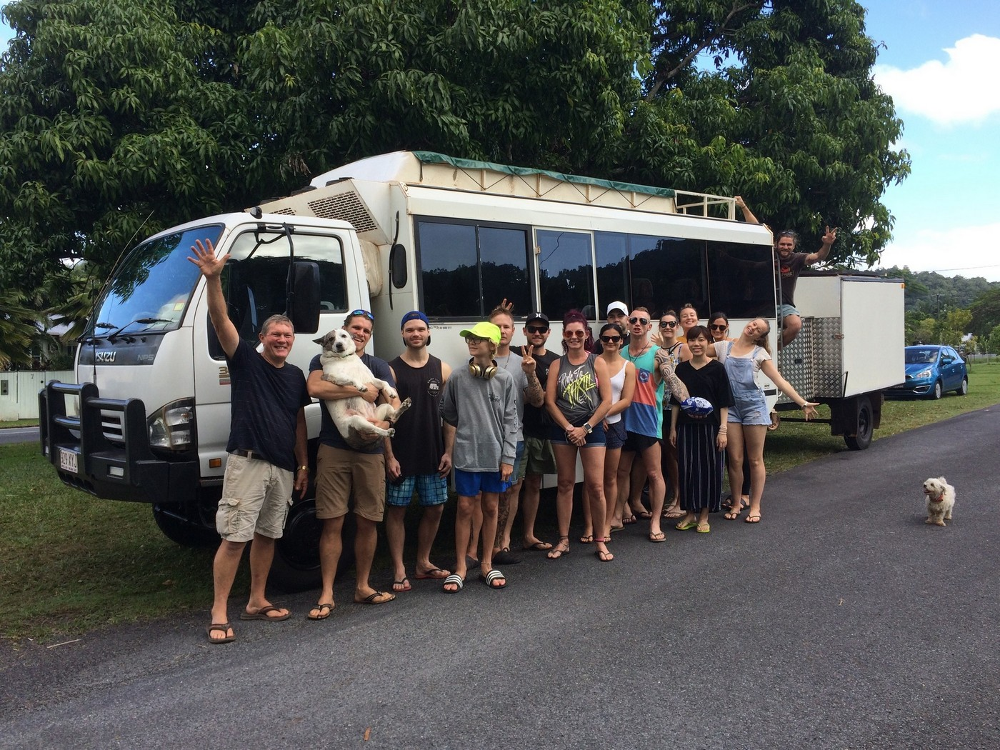 group of clients and workers next to tour bus.