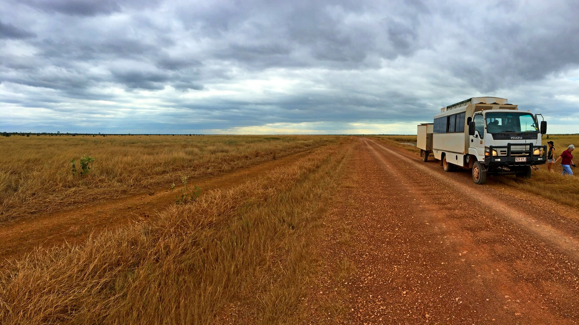 tour bus on dirt road in open plains.