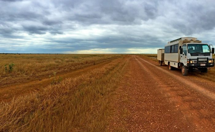 tour bus on dirt road in open plains.