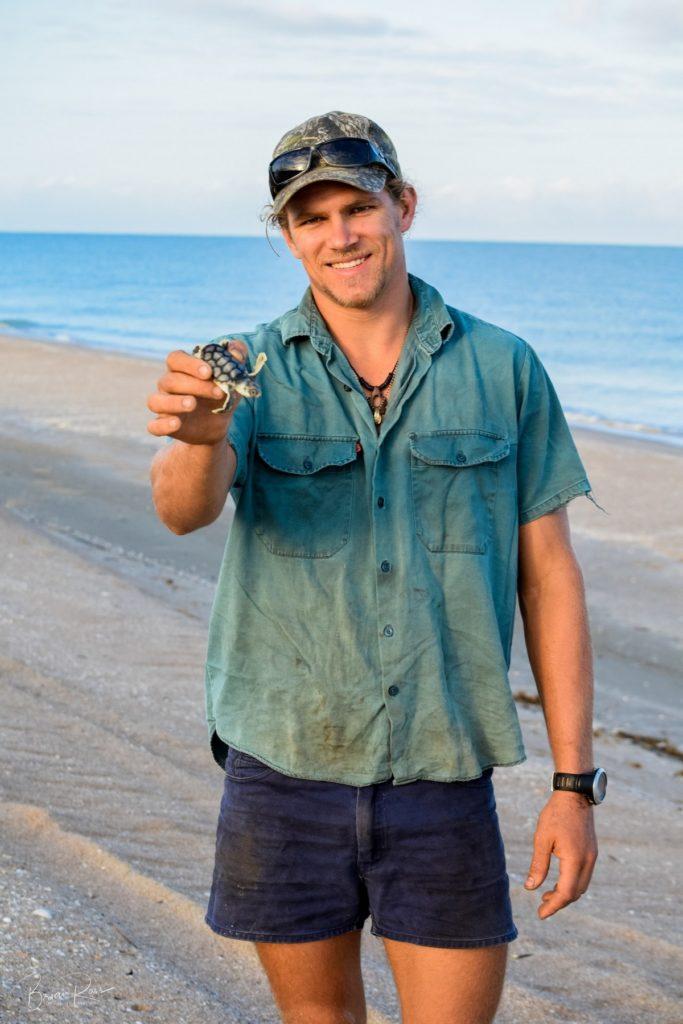 Man holding baby turtle