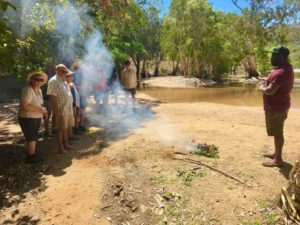 Indigenous man with fire and people