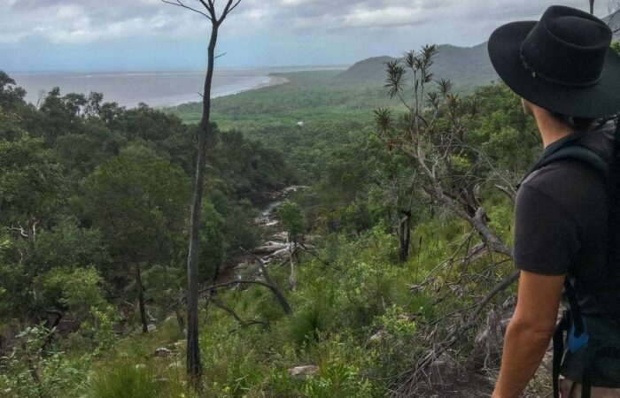 Man looking at ocean from mountains