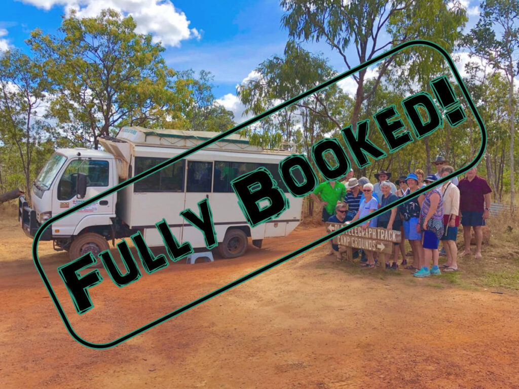 cape york tour bus and group of people next to 4wd sign