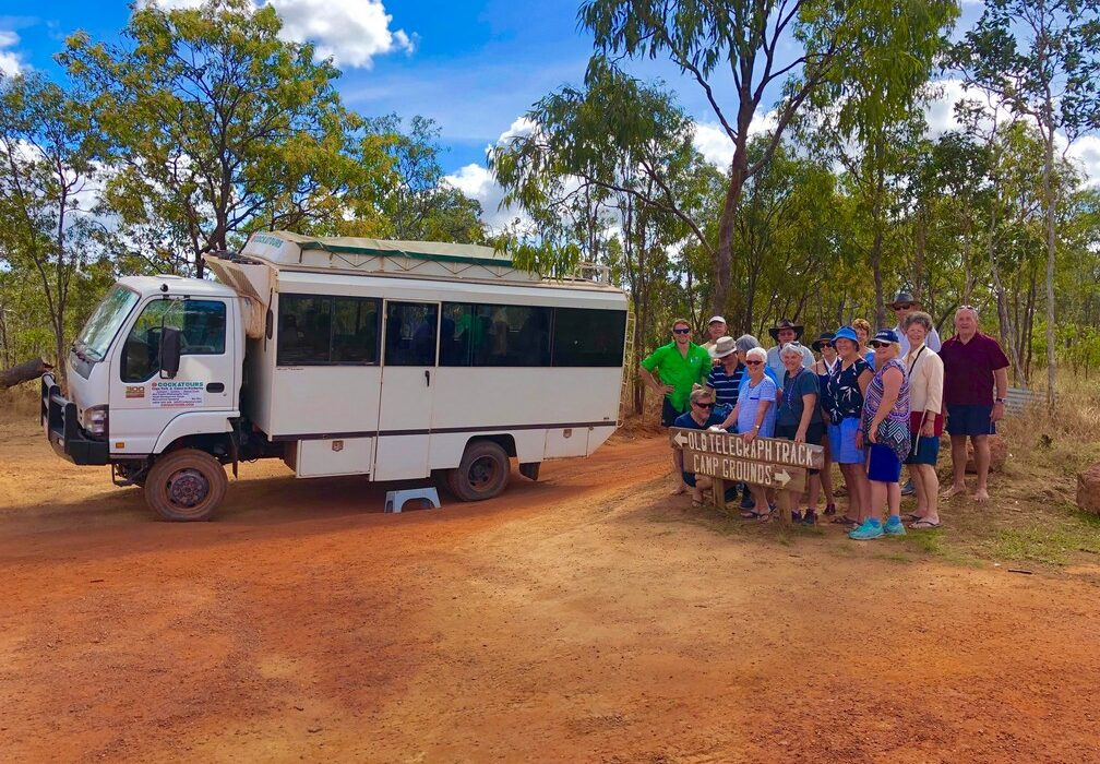 bus and group of people next to 4wd sign